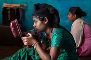 After washing her hair, Jyoti, 14, (left) is checking herself in the mirror while her younger sister Pooman, 13, is sitting next to her, on the floor of their newly built home in Oriya Basti, one of the water-contaminated colonies in Bhopal, central India, near the abandoned Union Carbide (now DOW Chemical) industrial complex, site of the infamous '1984 Gas Disaster'.