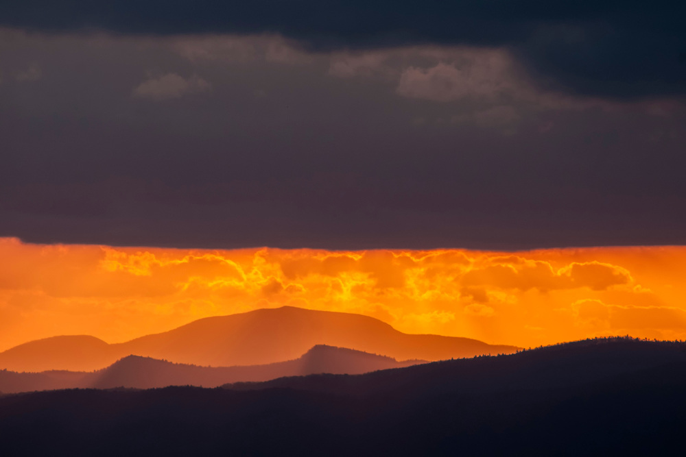 A break in the clouds near the horizon brings out the warm sunset colors at the scenic overlook on Sassafras Mountain in Sunset, SC on Friday, February 24, 2017. Copyright 2017 Jason Barnette