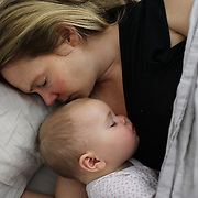 A nine month old baby girl is cuddled by her mother while asleep in bed. Photo Tim Clayton