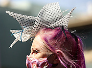 A spectator watches the jockies get on their horses before the start of a race at Santa Anita Park on April 3, 2021 in Arcadia, California.