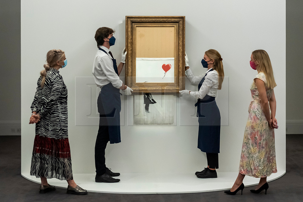 """© Licensed to London News Pictures. 03/09/2021. LONDON, UK.  **UNDER EMBARGO UNTIL FRIDAY 3 SEPTEMBER 2021, 12PM BST** Sotheby's staff view technicians presenting """"Love Is in the Bin"""" by Banksy at a preview at Sotheby's.  The painting, originally known as """"Girl with Balloon"""", was famously shredded by the artist in Sotheby's London auction room in 2018 after being sold for £1,042,000.  The resulting artwork was later renamed """"Love Is in the Bin"""" and will be offered for sale in Sotheby's contemporary art evening auction on October 14 with an estimate of £4-6 million.  Photo credit: Stephen Chung/LNP"""