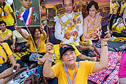 05 MAY 2104 - BANGKOK, THAILAND:  Thai supports of the monarchy with photos of Bhumibol Adulyadej, the King of Thailand. Thousands of Thais packed the area around Sanam Luang and the Grand Palace Monday evening for a special ceremony to mark Coronation Day, which honored the 64th anniversary of the coronation of Bhumibol Adulyadej, the King of Thailand. Many of the people also support the anti-government movement led by Suthep Thaugsuban. Most of the anti-government protesters are conservative supporters of the monarchy.   PHOTO BY JACK KURTZ