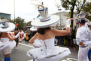 Hackney carnival 2014. The procession started in Ridley Road and passed by the The Hackney Town Hall with thousands of spectators lining the road. A group of dancers wear tea cups and pots as hats inspired by Alice in Wonderland.