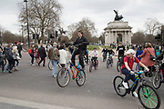 Thousands of cyclists from Bike Life, and one here with a modified bike made from two frames, on a mass ride-through block the street and wheelie their cycles around Hyde Park Corner in London, United Kingdom. This was like a flash mob event, where suddenly the whole street was filled with bicycles that took over the streets.