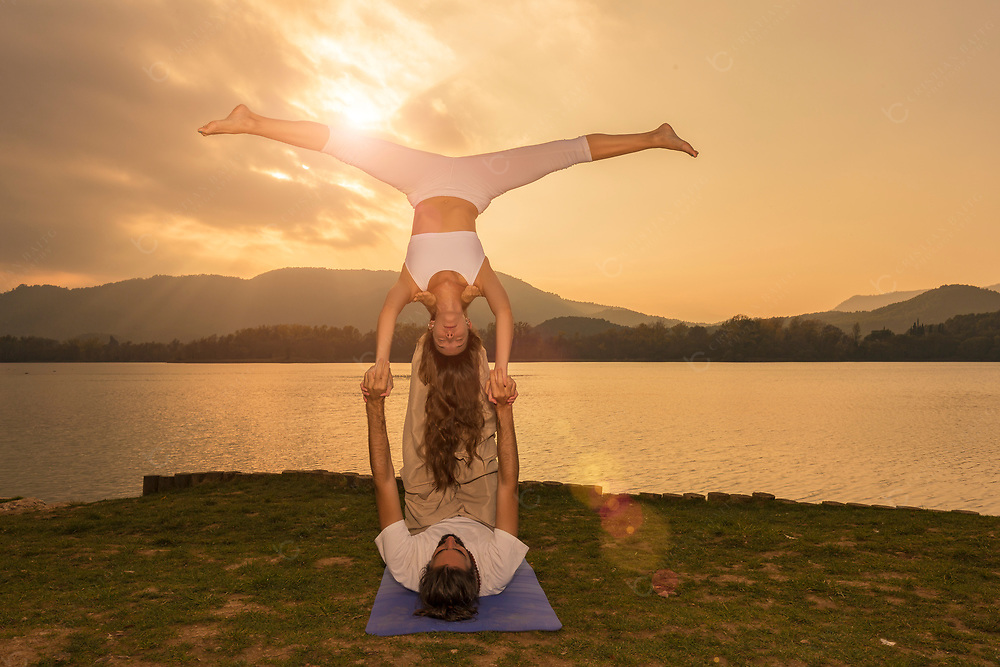 Man and woman doing a Pike star acroyoga pose during sunset