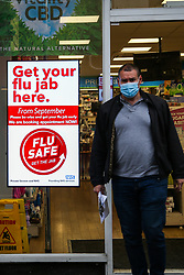 © Licensed to London News Pictures. 13/10/2020. London, UK. A man wearing a face covering walks past a 'Flu Jab' advert in north London. According to research, a flu jab  could offer some vital protection against Covid-19. GPs and pharmacies are to vaccinate almost 30 million people in England against flu in the next two months to help prevent the health service collapsing under the joint burden of a flu outbreak and Covid-19. Photo credit: Dinendra Haria/LNP