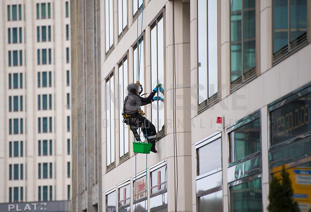 DEU, Deutschland, Germany, Berlin, 02.04.2020: Zwei Industriekletterer hängen an Seilen und putzen die Fenster eines Geschäftshauses am Potsdamer Platz.