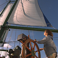 Madeleine Habib, third mate aboard the RAINBOW WARRIOR II, at the wheel as the ship sails towards the French nuclear test site of Muroroa atoll to protest against French President Chirac's decision to resume nuclear testing at the atoll in September. South Pacific. Accession #: 2.95.205.023.14