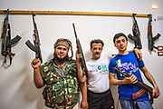 Kalashnikov assault rifles hang on the wall as Free Syrian Army (FSA) members hold their personal rifles and pose for a picture at the FSA facilities in Marea on Monday, May 28, 2012. (Photo by Vudi Xhymshiti)