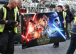 © Licensed to London News Pictures. 16/12/2015. London, UK. Workers carry a poster in Leicester Square ahead of the UK premiere of Star Wars: The Force Awakens. Photo credit: Peter Macdiarmid/LNP