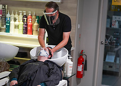 © Licensed to London News Pictures. 04/07/2020. Sheffield , UK. Conrad Blandford, owner of Conrad Blandford Hairdressing salon, Sheffield wears PPE (Personal Protective Equipment) and a protective face mask as washing a client's hair as lockdown ease allows hair salons to reopen across the UK. Owner of Conrad Blandford Hairdressing salon has auctioned their first haircut post lockdown, raising a staggering £180 to be donated to the NHS as part of their 72nd birthday celebrations. Pubs, restaurants, hair salons, theatres, museums and galleries will reopen on July 4th, following a nationwide lockdown against the spread of the coronavirus disease. Photo credit: Ioannis Alexopoulos/LNP