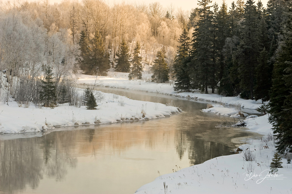 Open water of Junction Creek with frosted trees and reflections, Lively, Ontario, Canada