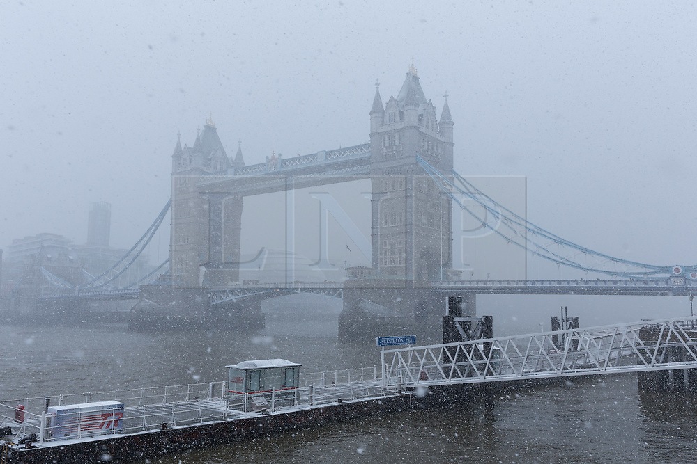© Licensed to London News Pictures. 27/02/2018. London, UK. A heavy snow shower next to Tower Bridge in London this afternoon. Following the snow shower, the capital saw bright sunshine and clear sky. Photo credit: Vickie Flores/LNP