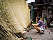 "29 DECEMBER 2018 - BANGKOK, THAILAND: A man fans a charcoal brazier he uses to speed the drying of longevity noodles in front of his family shophouse. The family has been making traditional ""mee sua"" noodles, also called ""longevity noodles"" for three generations in their home in central Bangkok. They use a recipe brought to Thailand from China. Longevity noodles are thought to contribute to a long and healthy life and  are served on special occasions, especially Chinese New Year, which is February 4, 2019. These noodles were being made for Chinese New Year.       PHOTO BY JACK KURTZ"