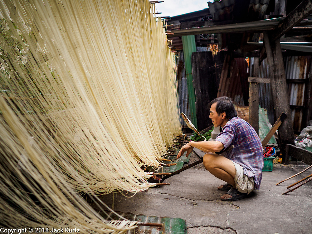 """29 DECEMBER 2018 - BANGKOK, THAILAND: A man fans a charcoal brazier he uses to speed the drying of longevity noodles in front of his family shophouse. The family has been making traditional """"mee sua"""" noodles, also called """"longevity noodles"""" for three generations in their home in central Bangkok. They use a recipe brought to Thailand from China. Longevity noodles are thought to contribute to a long and healthy life and  are served on special occasions, especially Chinese New Year, which is February 4, 2019. These noodles were being made for Chinese New Year.       PHOTO BY JACK KURTZ"""