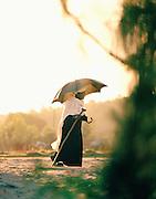 Elderly woman walking with a sun shade umbrella in Lalibela, Ethiopia