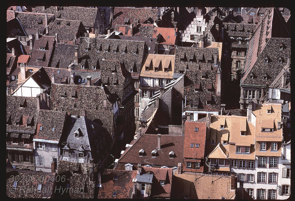 View atop the Cathedral of the jumble of tile roofs on buildings & homes in center of Strasbourg. France
