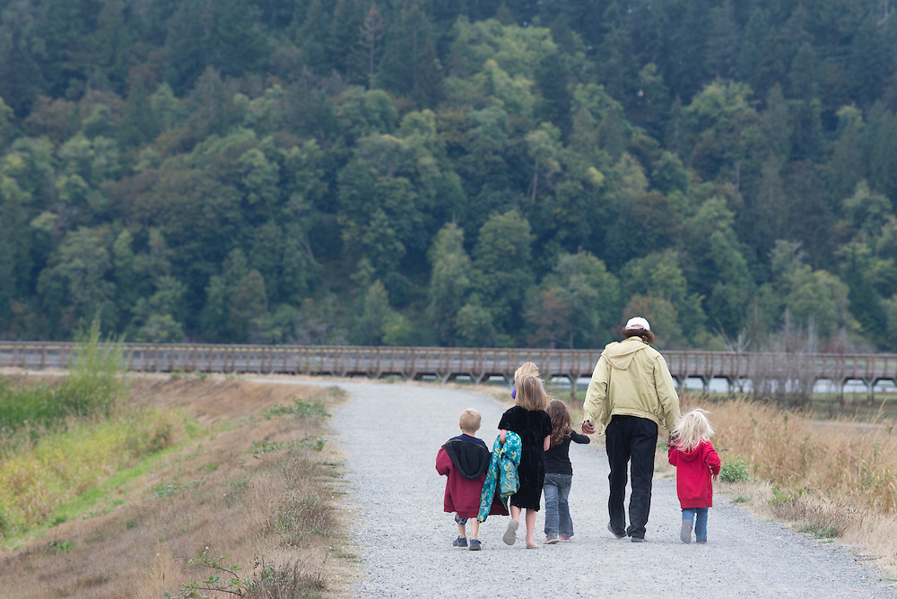 Family walking on a dike trail at the Billy Frank Jr. Nisqually National Wildlife Refuge in Western Washington.