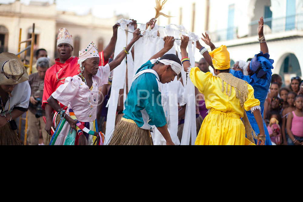 Male and female Cubans of African and mixed descendancy varying ages enacting a traditional ceremony wearing colourful costumes, performance in Havana old town, local dance and theatre group enacting the slave trade, colonial rule and how African religion and beliefs continuing, becoming what is now Santeria.