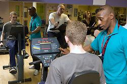 Trainer showing young man how to use the upright fitness bike at Southglade Leisure Centre; Nottingham