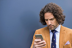 SMS young businessman long curly hair cell phone