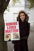 One woman protest against the mainstream keeping of domestic cats in the UK and the resulting increased probability of them killing songbirds on 4th December 2018 in London, United Kingdom. The woman holds a placard with a photograph of a robin and the text Robins Lives Matter in reference to the Black Lives Matter movement, and commenting that these birds also have a right to not be stalked and killed by pets.