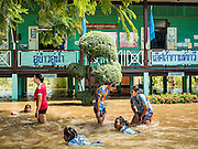 30 SEPTEMBER 2016 - SAI NOI, AYUTTHAYA, THAILAND:  A teacher plays in floodwaters with students at the flooded Wat Boonkannawas School. The Chao Phraya River, the largest river that runs through central Thailand, has hit flood stage in several areas in Ayutthaya and Ang Thong provinces. Villages along the river are flooded and farms are losing their crops due to the flood. This is the same area that was devastated by floods in 2011, but the floods this year are not expected to be as severe. The floods are being fed by water released from upstream dams. The water is being released to make room for heavy rains expected in October.     PHOTO BY JACK KURTZ