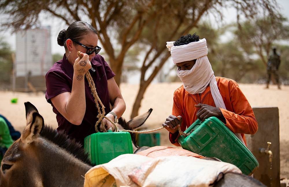 U.S. Army Staff Sgt Cana Garrison, with the 411 Civil Affairs Battalion, stationed at Air Base 201, helps a local Nigerien attach water jugs filled by a solar powered well to their donkey to transport back to their home.