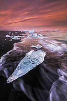 Water pattern caused by receding wave encircles a stranded iceberg at sunsest along the beach at Jokulsarlon, Iceland