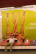 A man in sunglasses sitting on a bench in the Paris metro in front of a publicity poster. The poster has the text the least expensive brands all year round and the picture shows two young pretty women lying on their back with their legs stretched upwards and spread apart each woman only wearing one shoe and holding hands. Paris, France, Europe