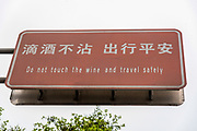 Do not Touch the Wine and travel safely a sign in Chinese and English Photographed in Dujiangyan city, Sichuan Province, China