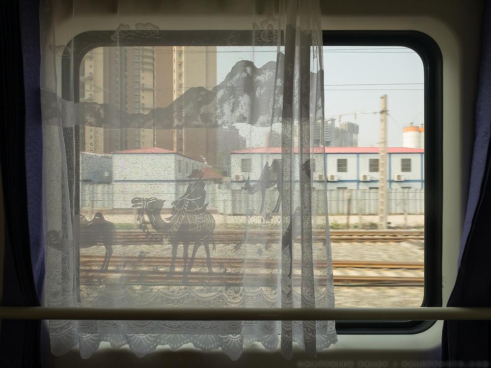Suburbs of Xian watched through curtains depicting a typical Xinjiang desert landscape. Window view across China, from Hong Kong to Urumqi, Xinjiang.