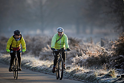 © Licensed to London News Pictures. 02/12/2019. London, UK. Two woman ride their bikes as frost covers the landscape at sunrise in Richmond Park in west London on a bright and freezing Winter morning. Photo credit: Ben Cawthra/LNP