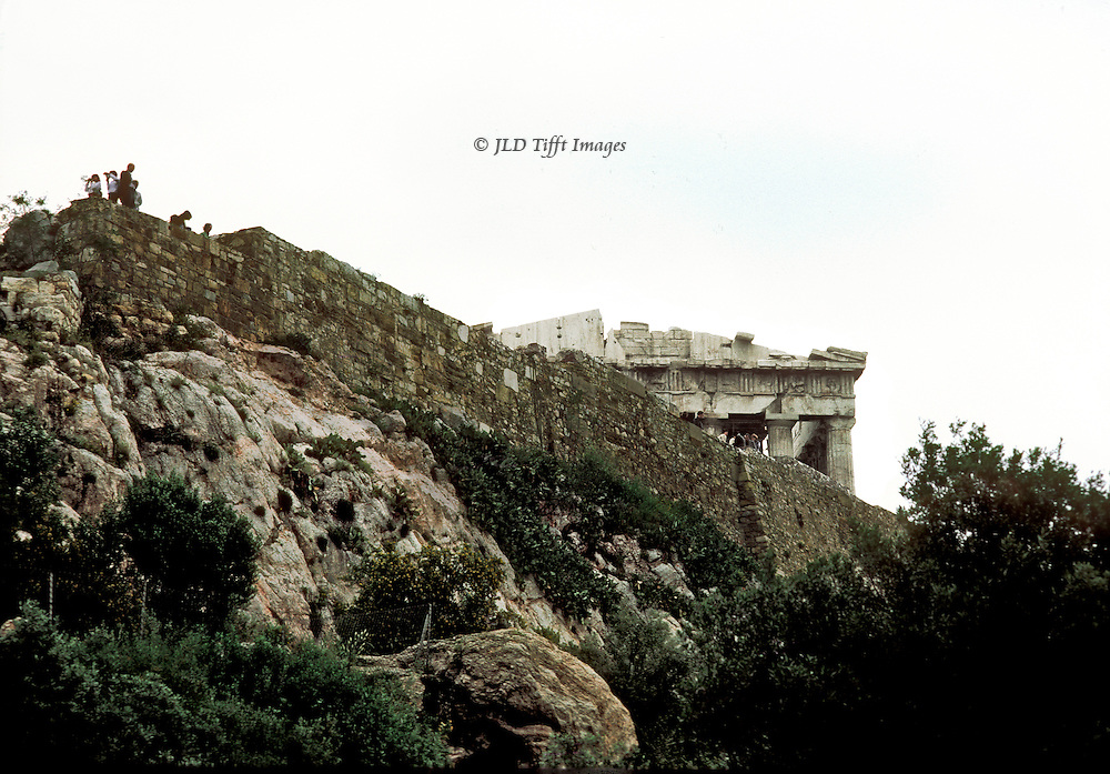 Approaching the Acropolis, the Parthenon roof and entablature appear peeking over the heights.