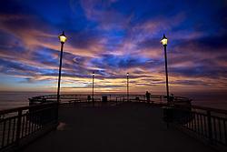 May 6, 2019 - Christchurch, New Zealand - A man catches fish as clouds above the beach and pier light up dramatically during the sun rises at New Brighton Beach in Christchurch, New Zealand on May 05, 2019. (Credit Image: © Sanka Vidanagama/NurPhoto via ZUMA Press)