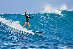 Woman surfer, riding a rare big ocean wave in Kona Coast, Keauhou Bay, Big Island, Hawaii, Pacific Ocean.