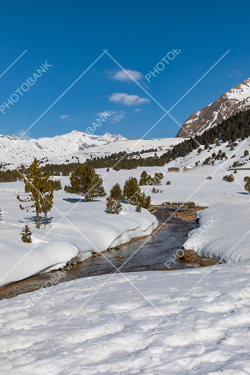 Panorama with lots of snow on Lukmanier in Ticino, on the Swiss Alps and a romantic stream through the landscape. Nobody inside