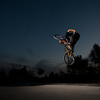 Strobe-lit freestyle BMX action, late evening at the Eagle Bike Park.
