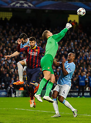 Man City Goalkeeper Joe Hart (ENG) punches a cross clear away from Barcelona Defender Gerard Pique (ESP) - Photo mandatory by-line: Rogan Thomson/JMP - Tel: 07966 386802 - 18/02/2014 - SPORT - FOOTBALL - Etihad Stadium, Manchester - Manchester City v Barcelona - UEFA Champions League, Round of 16, First leg.