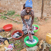 CAPTION: Namusisi is seen here doing laundry. Despite being hearing impaired and mute, she has found Damyano - whose impairments are very similar to her own - and the pair have married and now have two children. Through sign language, she shares that she leads a contented life, and attributes much of this to the help of SignHealth Uganda. LOCATION: Kankamba Village, Lwengo District, Central Region, Uganda. INDIVIDUAL(S) PHOTOGRAPHED: .