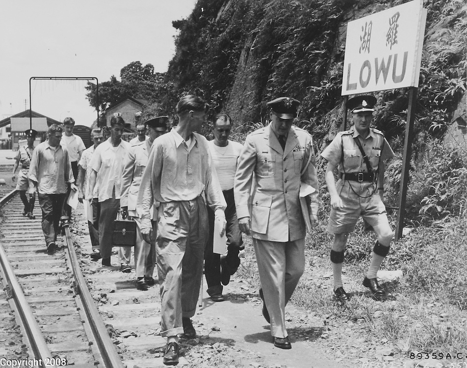 """Minutes after being freed by the Chinese Communists, 11 crew members of the B-29 """"Superfort"""" shot down during a leaflet-dropping mission over North Korea in January 1953, walk to freedom at Hong Kong. Leading the group is Col. John K. Arnold, Jr., left, accompanied by Lt. Col. O.D. Simpson, air attache at Hongkong. The group was taken later to the Jockey Club in the Hongkong crown colony, received new, clean clothes, took shower baths and enjoyed their first meal since freedom, a steak dinner with all the trimmings. 6 August 1955"""
