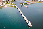 High-angle, aerial view of the Kewaunee Lighthouse, Kewaunee, Wisconsin, with a boat entering the harbor.