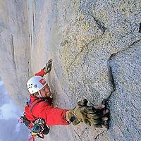 BAFFIN ISLAND, NUNAVUT, CANADA. Alex Lowe (MR) prepares for hook moves, aid climbing high on Great Sail Peak.