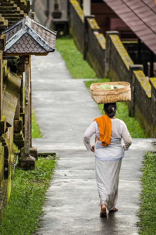 Stock photograph of a Balinese lady walking toward the temple to celebrate Nyepi at Besakih in Bali