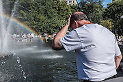 A man cools off beside a rainbow in the fountain in Washington Square Park on a hot summer day.