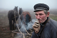 Romanian Hungarian farmer having a cigarette while taking a break from plowing the land.