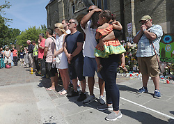 People observe a minute's silence near to Grenfell Tower in west London after a fire engulfed the 24-storey building on Wednesday morning.