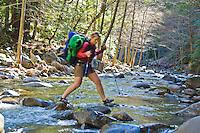 Backpacker crosses Big Sur River, Pine Ridge Trail, Big Sur, California.