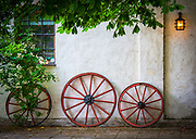 Old wagon wheels leaning towards wall of building in Yngsjö in Skåne, a southern province of Sweden