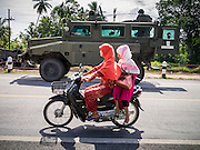 11 JULY 2013 - RAMAN, YALA, THAILAND: Muslim women ride their motorcycle past a Thai army REVA 4x4 MKII Armoured Personnel Carrier guarding the scene of an IED attack against a Thai Army unit. Eight soldiers were injured when the IED exploded under a Thai Army truck carrying soldiers back to their camp after they finished a teacher protection mision. The army routinely dispatches soldiers to protect teachers and Buddhist monks, who have been targeted by Muslim insurgents as representatives of the Bangkok government. More than 5,000 people have been killed and over 9,000 hurt in more than 11,000 incidents in Thailand's three southernmost provinces and four districts of Songkhla since the insurgent violence erupted in January 2004, according to Deep South Watch, an independent research organization that monitors violence in Thailand's deep south region that borders Malaysia.    PHOTO BY JACK KURTZ
